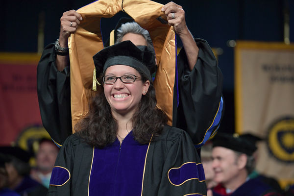 A doctoral student being hooded by her advisor at graduation