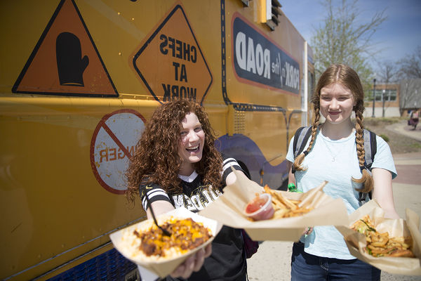 Kent State students show off food purchased from 餐饮服务' Fork in the Road Food Truck.