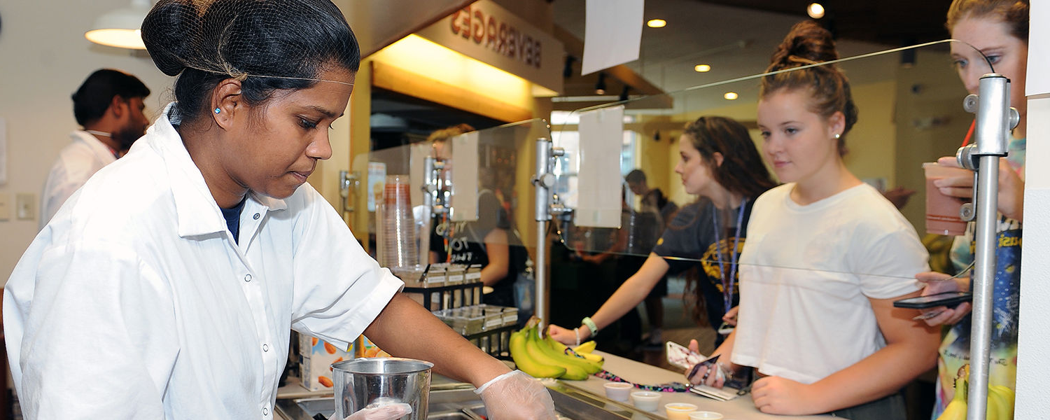 A food service employee mixes a smoothie for a student in the exclusively gluten free Prentice Hall Café.