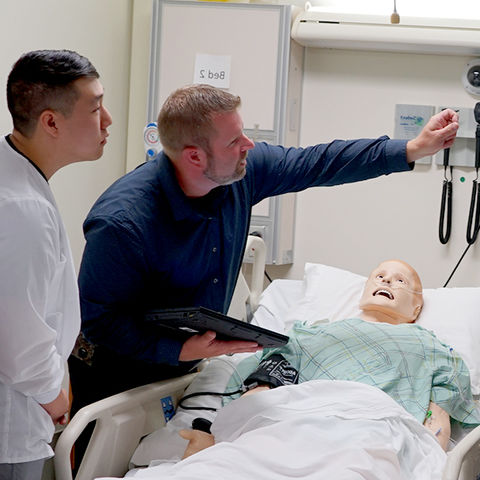Jeremy Jarzembak explains a simulation mannequin's vitals to students