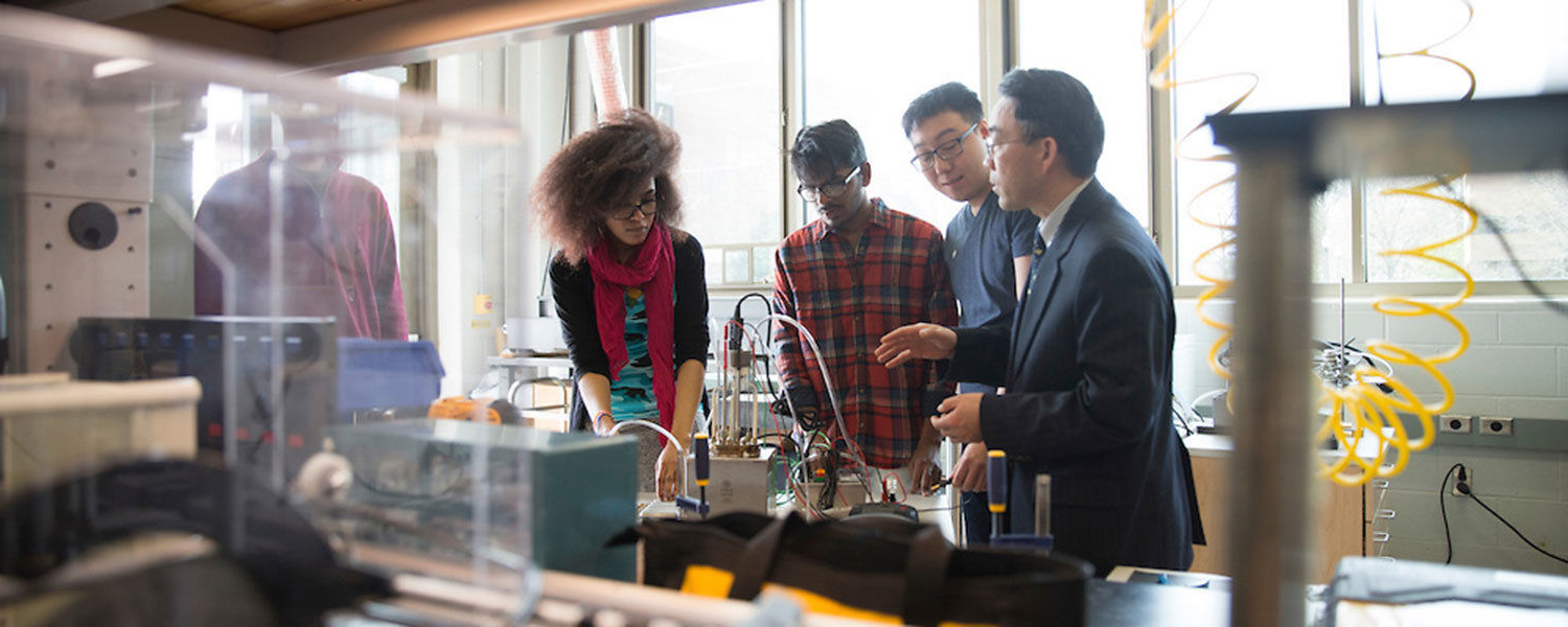 Students gather near a professor during lab sessions.