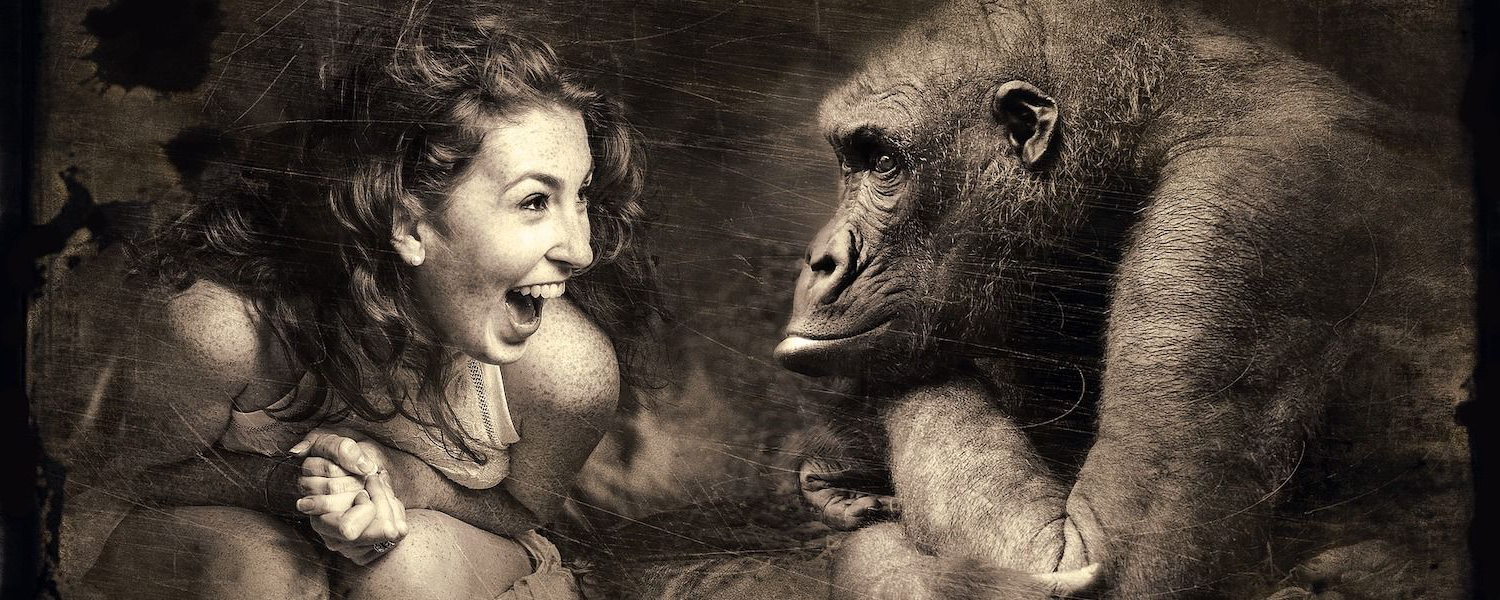 An artful black and white image of a human woman sitting and laughing with a gorilla.